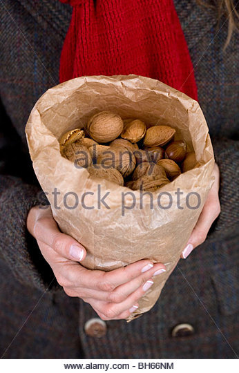 A woman holding a bag full of mixed nuts - Stock Image