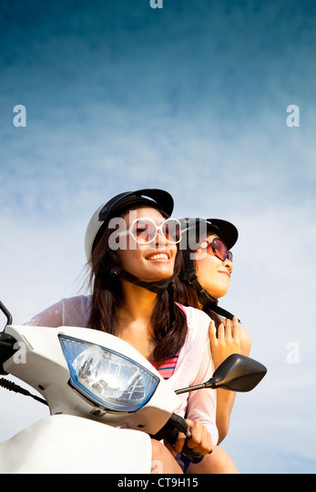 young woman riding scooter on the sunny day - Stock-Bilder