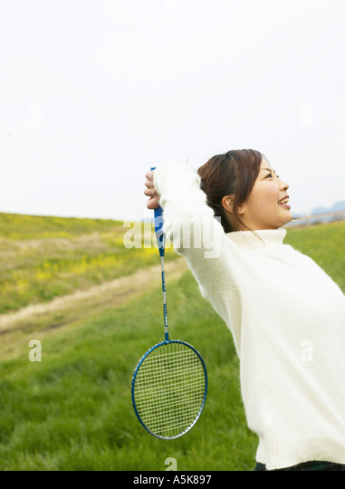 Young woman playing badminton - Stock Image