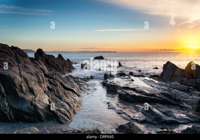 Sunrise at a rock beach at Looe in Cornwall - Stock Image