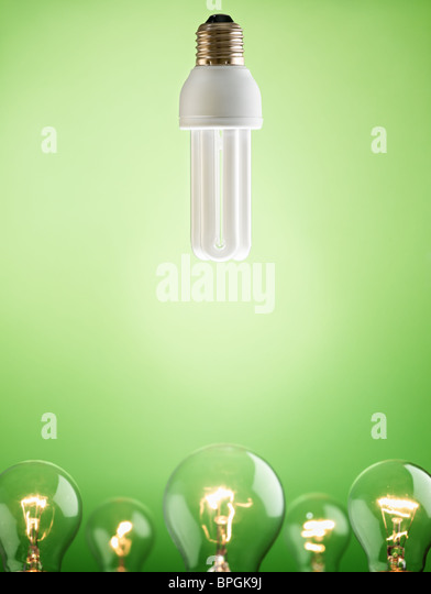 fluorescent lightbulb over large group of tungsten lights on green background. Vertical shape, copy space - Stock Image