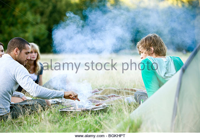 A group of young friends having a barbecue outdoors next to a tent - Stock Image
