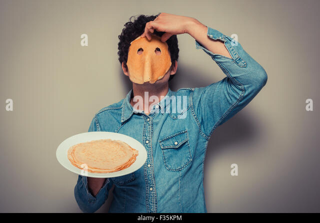 Young man has cut eyeholes in a pancake and is wearing it on his face - Stock Image