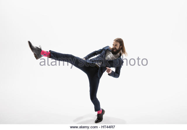 Aggressive businessman with beard kicking in fighting stance against white background - Stock-Bilder