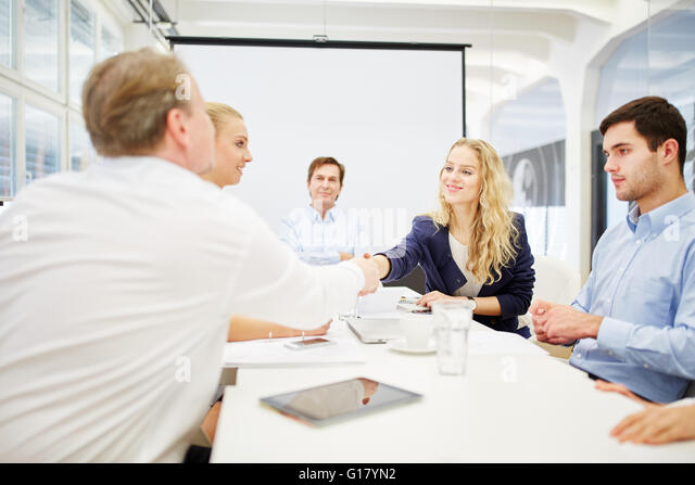 Business people achieve an agreement and shake hands - Stock Image