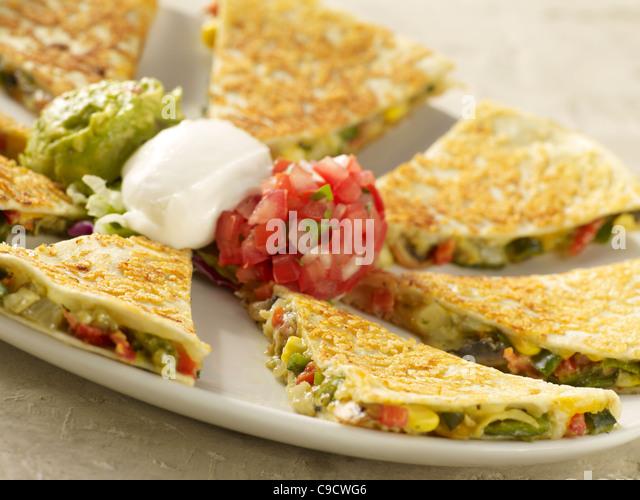 A vegetable quesadilla with salsa fresca, sour cream and guacamole - Stock Image