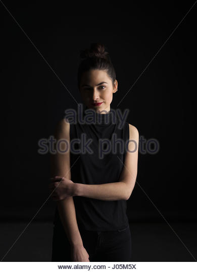 Portrait confident brunette woman in shadow against black background - Stock Image