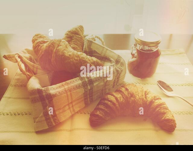 Small jar of homemade strawberry jam, bread basket with croissant, striped cloth and silver spoon. Warm, retro tones. - Stock Image