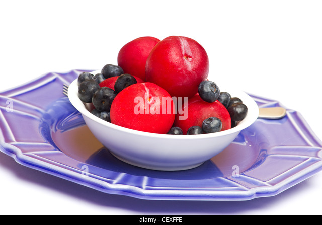 Fresh plums and blueberries in white bowl on white background - Stock Image