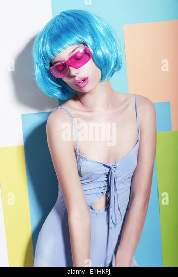 Eccentric Extravagant Woman in Styled Blue Wig and Pink Sunglasses - Stock Image