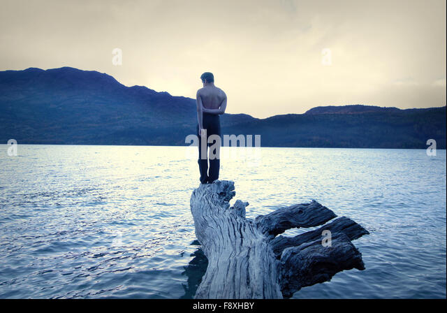 boy standing in a fallen tree in the middle of the water, stormy sky, vintage and conceptual - Stock-Bilder