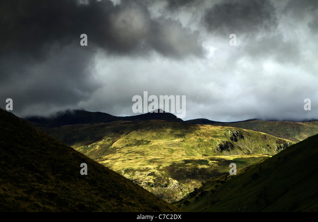 Black clouds over Helvellyn, the third highest mountain in the Lake District, taken from the path to Hayswater, - Stock Image