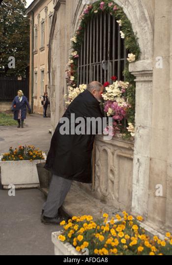 Ukraine L'vov L'viv St. George Greek Catholic Cathedral exterior man praying - Stock Image
