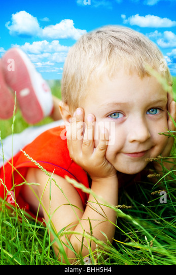 Portrait of happy cute child in the grass - Stock Image