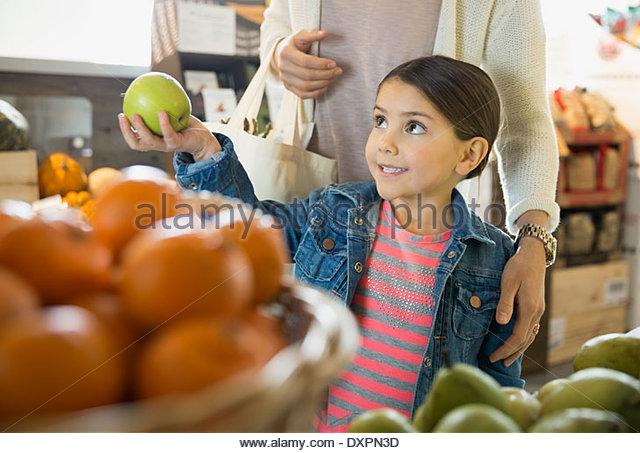 Daughter showing apple to mother in market - Stock Image