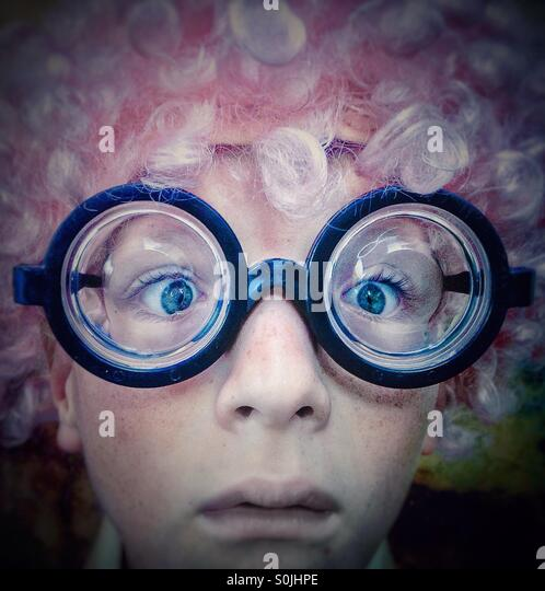 Portrait of a boy with pink wig and nerd eyes glasses looking at the camera - Stock Image