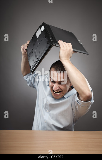 Extremely angry businessman smashing his laptop on the desk - Stock Image