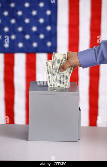 Hand putting money into ballot box, voting and bribery concept, American flag background - Stock-Bilder
