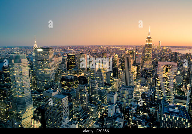Beautiful New York City Manhattan buildings lit up at sunset - Stock Image