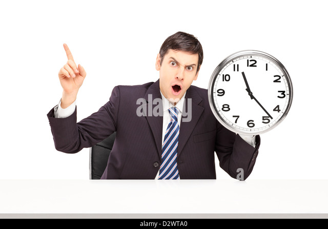 Angry businessman sitting and holding a wall clock isolated on white background - Stock Image