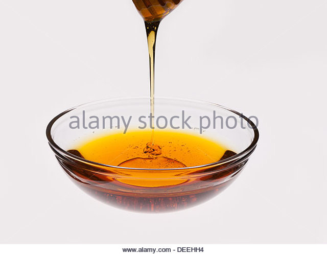 Honey dripping off honey dipper into bowl - Stock Image
