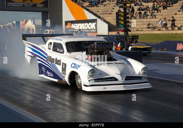Australian Top Doorslammer drag racing competitor, Robin Judd, performs a rolling burnout in his 1959 based Studebaker - Stock Image