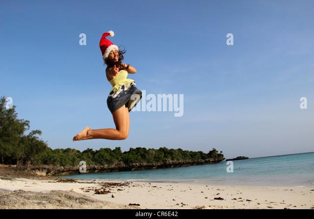 Africa, Tanzania, Teenage girl jumping at beach - Stock Image