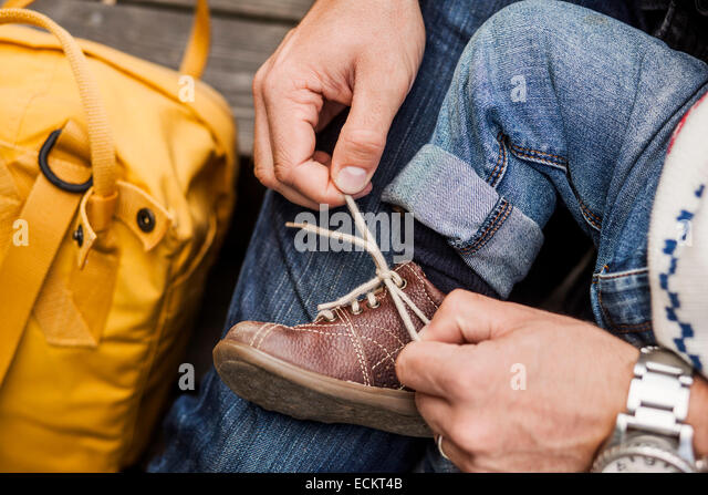 Cropped image of father tying shoe lace of baby girl - Stock Image