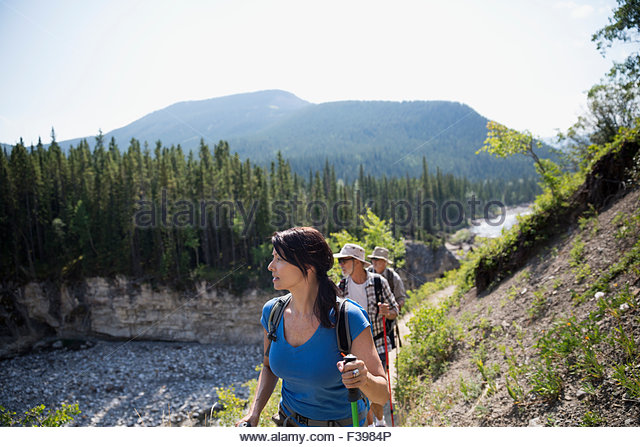 Hikers walking along craggy ridge above river - Stock Image
