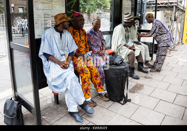 Men dressed in African costumes at a bus stop waiting for the Notting Hill Carnival parade, London, England, United - Stock Image