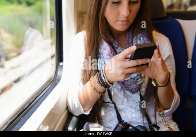 Young female tourist on traveling on local train, Catalonia, Spain - Stock Image