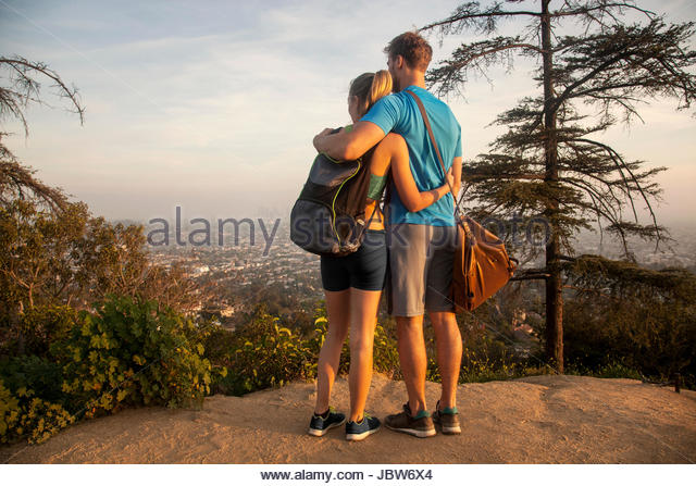 Man and woman outdoors, wearing sports clothing, standing on mountain, looking at view, rear view - Stock-Bilder