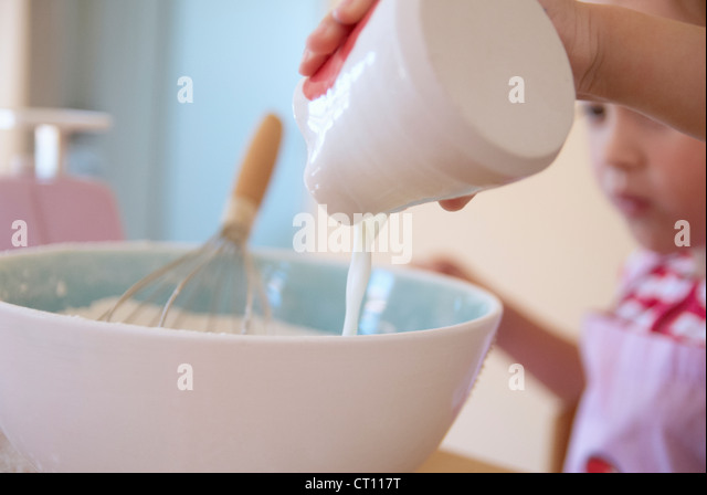 Girl pouring milk into batter in kitchen - Stock Image