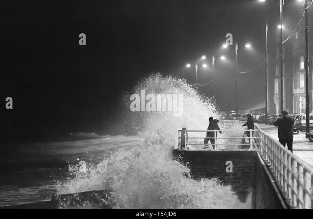 Aberystwyth, Wales, UK. 27th October, 2015. Teenagers take risks as the waves at high tide this evening crash against - Stock Image