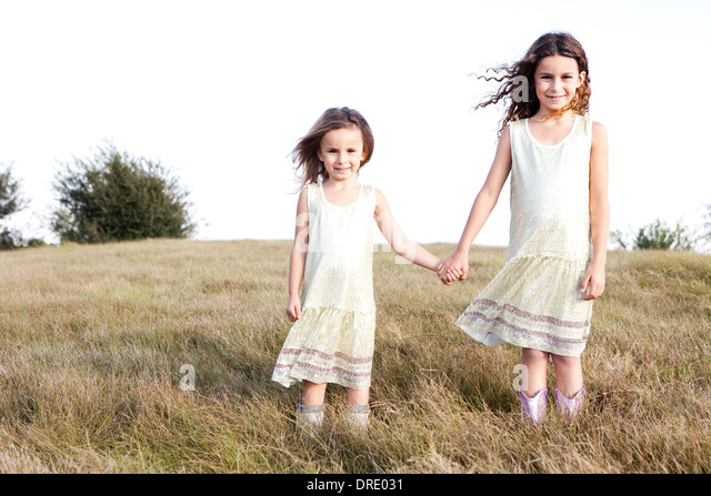 Sisters in dresses standing in field - Stock Image
