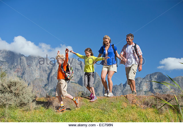Family hiking on a mountain path - Stock-Bilder