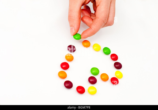 Laying down candy in a shape of a heart - Stock Image