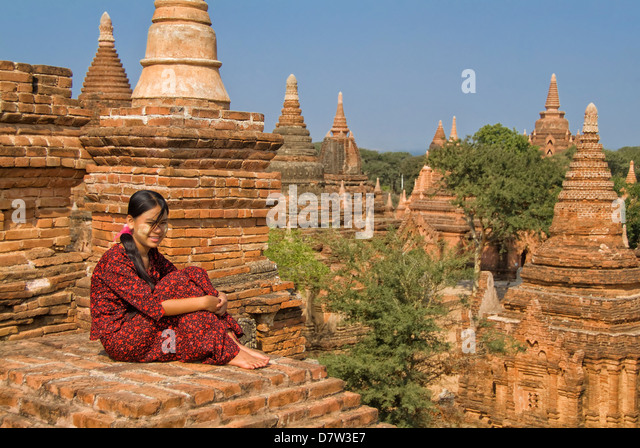 Young Burmese woman in a red dress sitting on the roof of a temple, Bagan (Pagan), Burma - Stock-Bilder