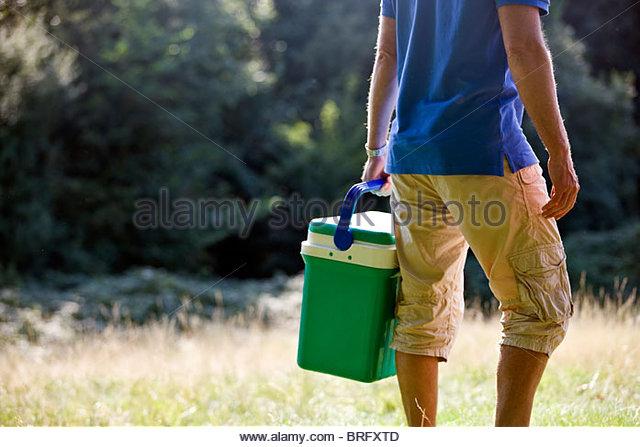 A man carrying a cool box, rear view - Stock-Bilder