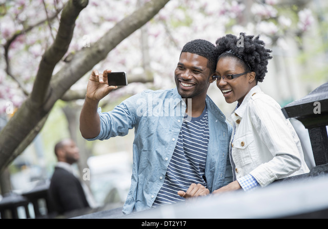 City in spring An urban lifestyle A couple side by side cheek to cheek taking a photograph with a handheld mobile - Stock Image
