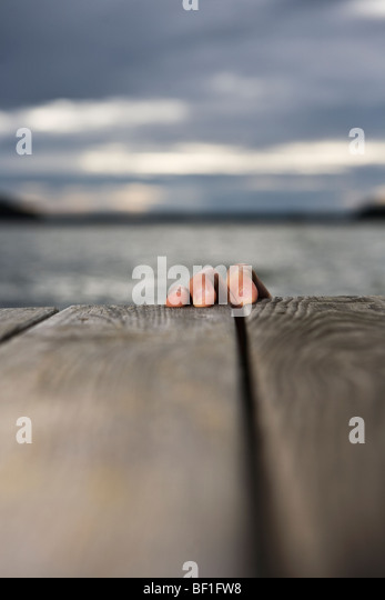 The fingers grasping the edge of a jetty, Sweden. - Stock Image