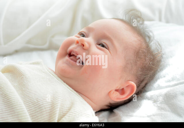 Face of a newborn baby smile in his baby cot. Concept photo of newborn, baby, mother, motherhood, parenting and - Stock Image