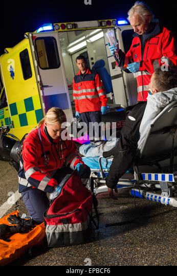 Paramedic team assisting injured motorbike driver - Stock Image