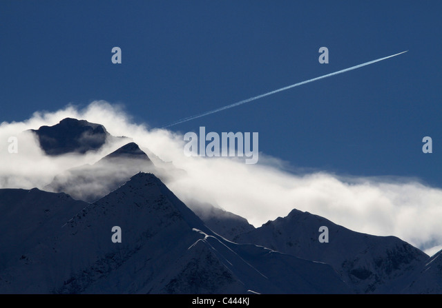 An airplane vapor trail over a mountain range, Graubunden Canton, Switzerland - Stock Image