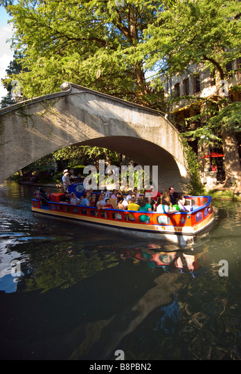 San Antonio River Walk above riverwalk tour boat with tourists passes under arched bridge crossing the San Antonio - Stock Image