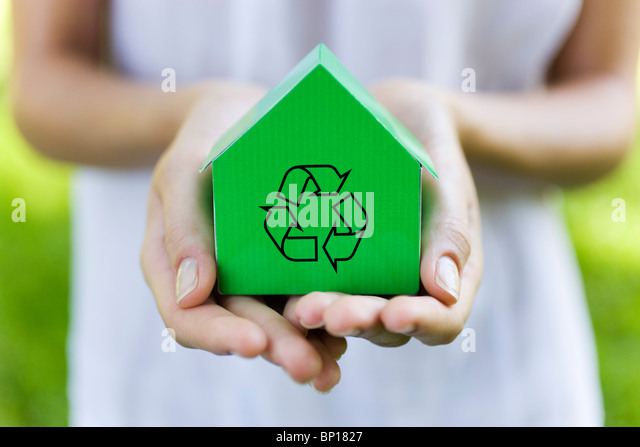 Young woman holding green model house with recycling sign - Stock Image
