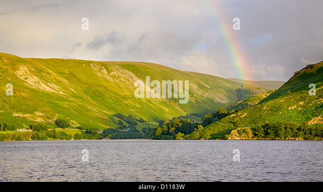 A rainbow provides a scenic backdrop to Ullswater, near Howtown Jetty in England's Lake District. - Stock Image