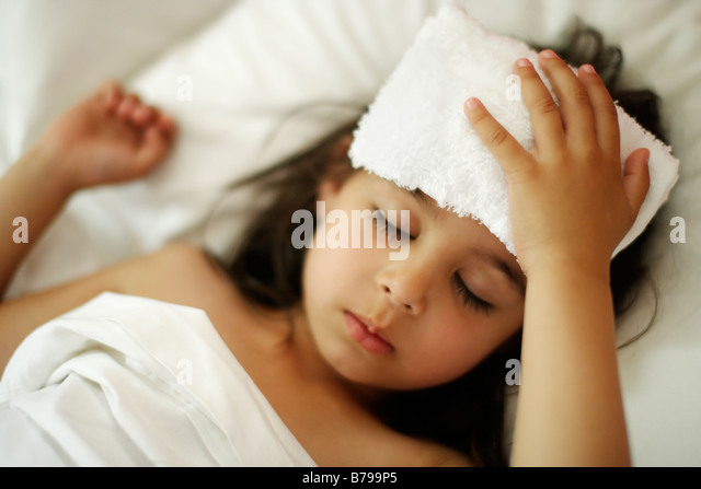 Five year old girl with cool flannel on head in bed with white sheets - Stock-Bilder