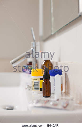 Toiletries and medication on sink in bathroom - Stock Image
