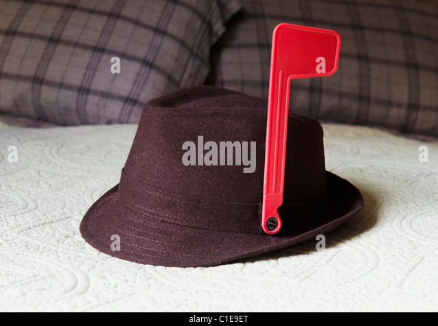 fedora on bed with mailbox alert flag attached to hat - Stock Image